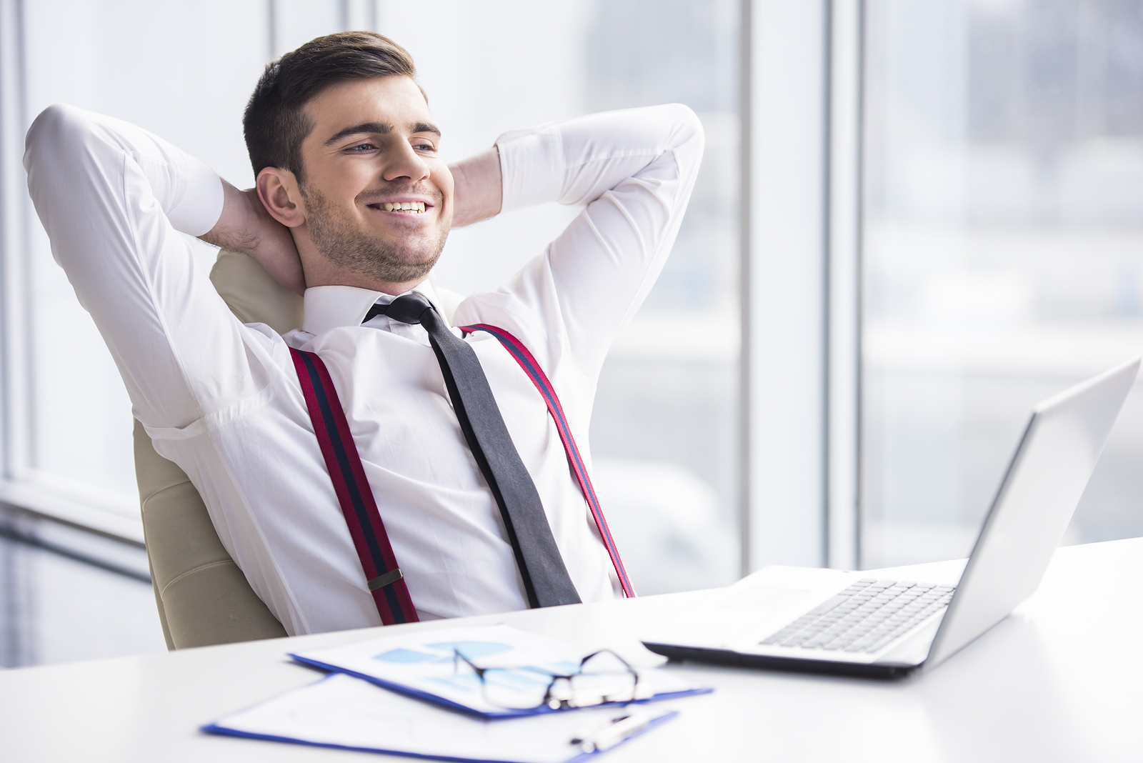 A time for relax. Young happy businessman is relaxing in his office.